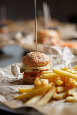 Tasty little baby burger in cafe menu.Fast food restaurant dish for little children.Small crafted hamburger served with golden French fries in cafe.Food close up