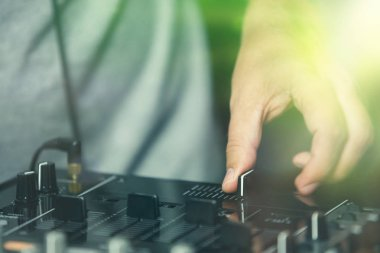 Professional hip hop dj holds crossfader knob while scratching musical tracks on party in nightclub.