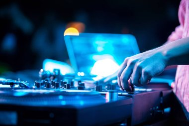 Hip hop party dj scratches vinyl records on turntable and cut tracks with cross fader knob on sound mixer.Professional disc jockey audio equimpent on stage in night club.Bright blue concert lights