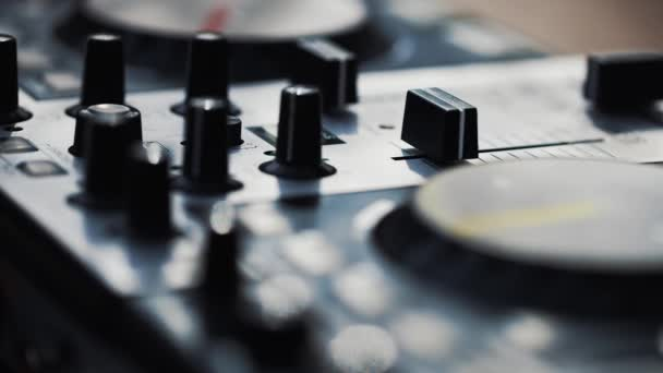 Footage of party dj mixer device on close up.Video of professional disc jockey audio equipment in close up.Mixing panel with volume regulators and cross fader to play music on concert in night club.