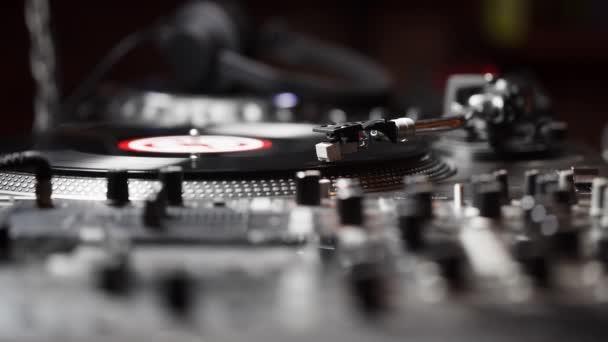 Záběry party DJ se v těsné blízkosti obrátí s jehlovou stříkačku na analogový vinylovou desku. Video o raménním tónu a kazetě s jehlami. Profesionální audio žokon pro koncert v nočním klubu.