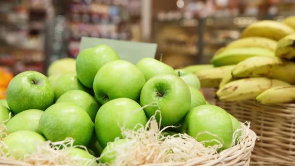 Footage of basket with fresh ripe green apple fruits on sale in grocery food store.Supermarket shop,natural foods department.Close up,focus on apples in box.Eat vitamins for strong health.
