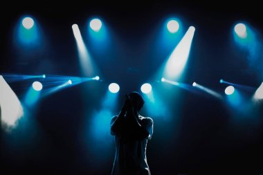 Rap singer with microphone on stage in music hall