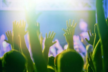 Concert crowd partying to the music performance on stage