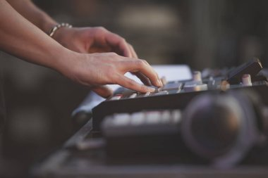 Hip hop beat maker playing beats on rap music concert with drum machine.Professional musician plays popular musical tracks on stage with midi controller.Stage audio equipment.EDM dj set in nightclub