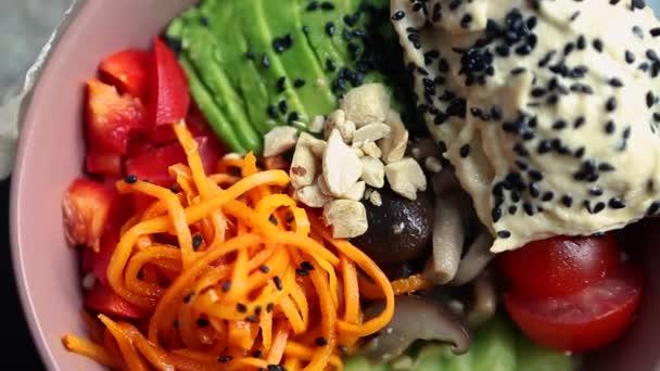 Poke mísa se zeleninou a hummus natočené na stole seshora. Video klip s přírodními ingrediencemi pro zdravé stravování.Vegetariánská snídaně jídlo připravené s čerstvými surovinami