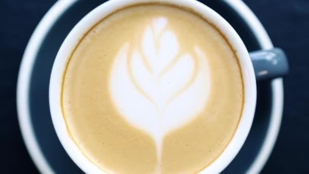 Kupa friss reggeli cappuccino kávé kerámia bögre filmezett közvetlenül felülről.Videóklip forró energetikai ital reggelire.Élvezze aromás olasz latte virágos rajz hab réteg