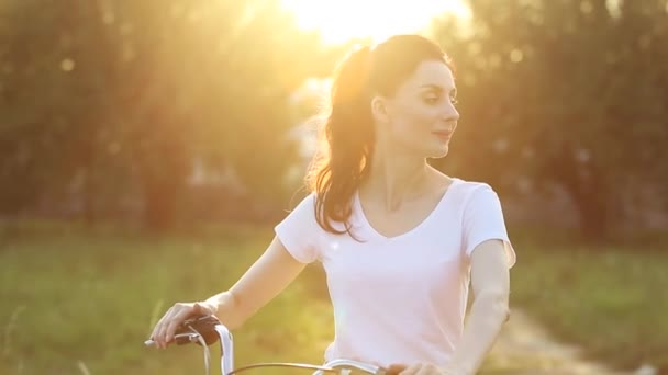 Happy young brunette woman with bicycle in sunny park at sunset