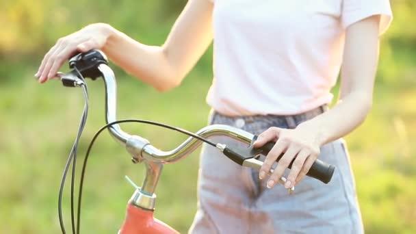 Dívka jede na kole při západu slunce v zeleném parku.