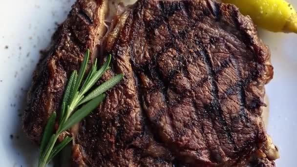 Grilovaný T-bone steak podávaný na bílém talíři v masové restauraci, natočený shora s efektem oddálení.Detailní videoklip z hovězího masa grilovaného s pepřem, rozmarýnové koření k večeři v kavárně