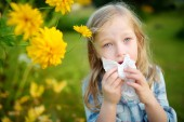 Cute little girl blowing her nose by beautiful yellow coneflowers on summer day. Allergy and asthma issues in small kids. Healthy living.
