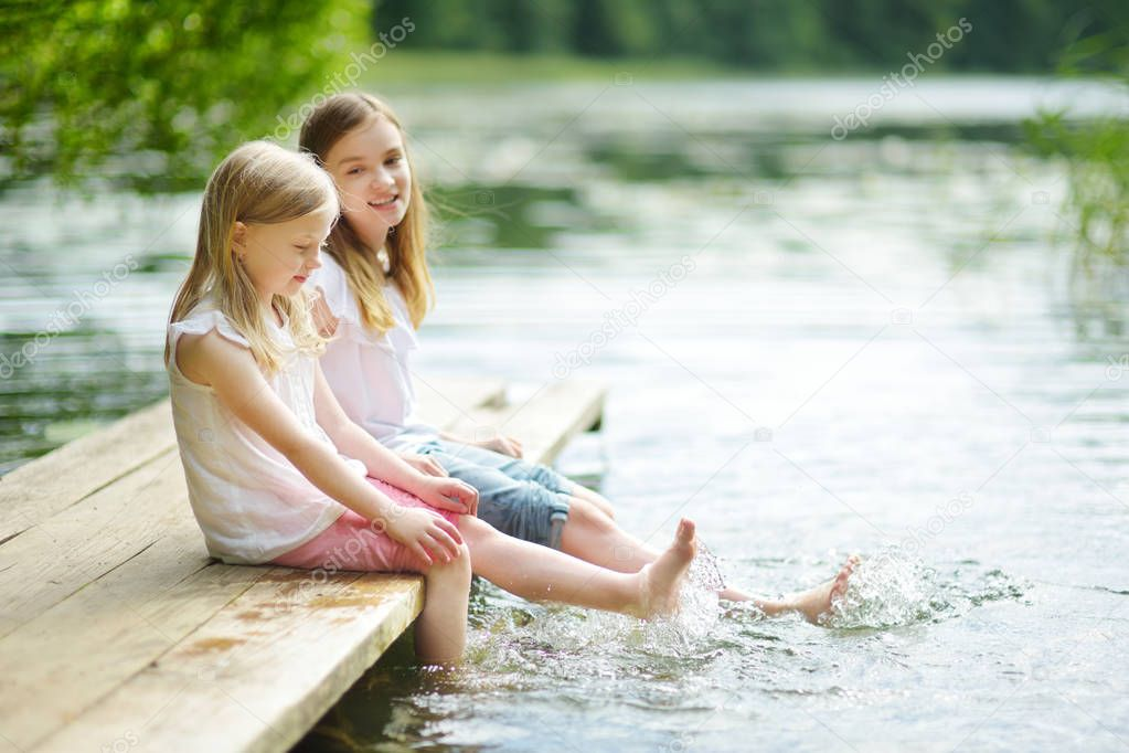 Two cute little girls sitting on a wooden platform by the river or lake dipping their feet in the water on warm summer day. Family activities in summer.