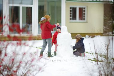 Cute little girls and their grandma building a snowman in the backyard. Cute children playing in a snow. Winter activities for kids.