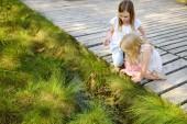 Zwei entzückende junge Mädchen fangen Baby Frösche im Sommerwald
