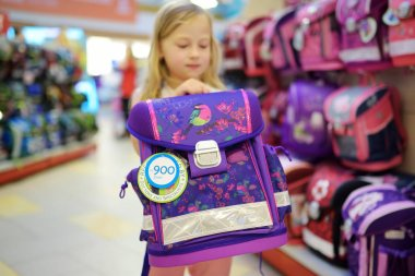 Cute little girl choosing schoolbag before starting classes