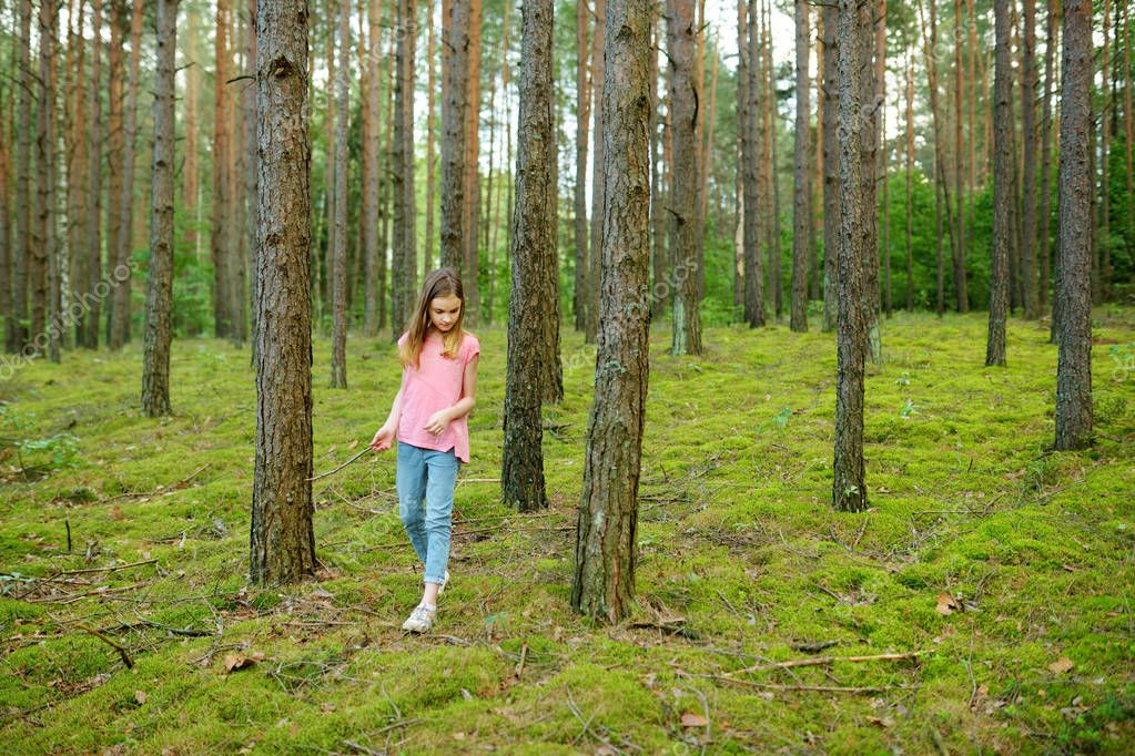 Cute young girl walking in forest at summer day