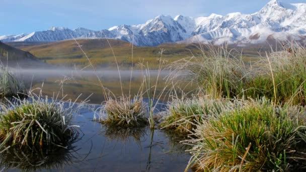 View on Altai lake Dzhangyskol on mountain plateau Eshtykel. North Chui ridge is reflecting in the water. Siberia, Russia