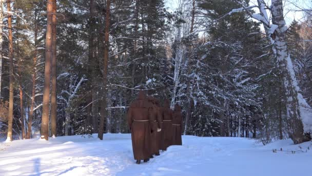 Group of monks pilgrims in hood robe walking along winter snow trail in forest