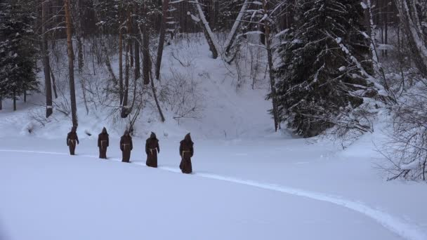 Group of monks in hood robe walking along winter snow trail in forest