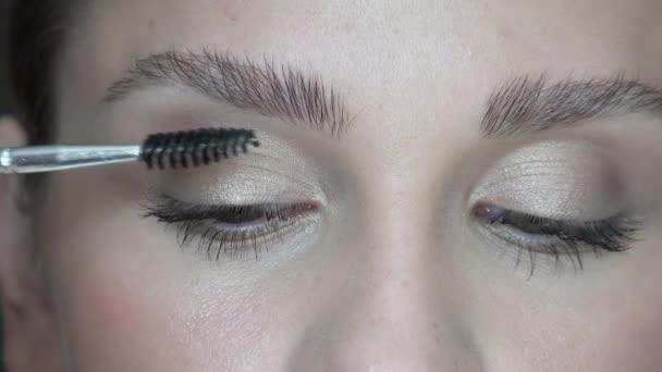Detail videa krásná mladá bruneta žena použití oční zónu tvoří s kosmetických štětců