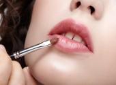 Vizážista aplikovat make-up beauty na rtech krásné dívky. Vizážistka s make-upu štětec v ruce