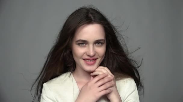 Slow motion video portrait of beauty young brunette smiling, woman portrait with green eyes and streaming hair in white fashion female jacket on gray background