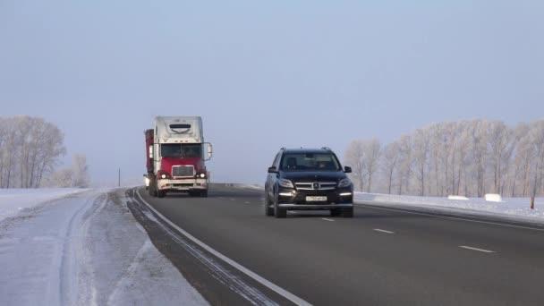 Altaj, Rusko - 18 ledna 2017: Freightliner a muž nákladních vozidel na silnici M52 Chuysky traktu v zimní sezóně