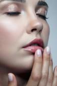 Detailní makro portrét ženské tváře s oči zavřené. Žena s přirozenou krásu make-up. Dívka s prsty blízko obličeje