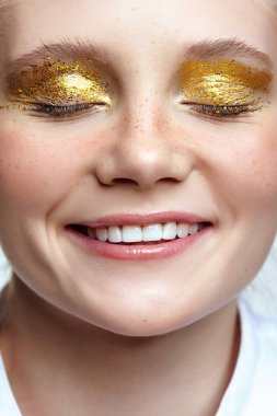 Smiling female face with closed eyes. Woman with unusual glitter glitzy vogue face beauty makeup. Girl with perfect skin and yellow smoky eyes eye shadows