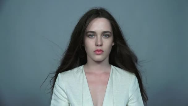 Video portrét portrét mladá bruneta žena krásy se zelenýma očima a datových proudů vlasy v bílé módní žena bunda na šedém pozadí