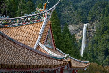 Curved roofs of colorful Chinese temple and Nachi waterfalls on