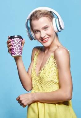 Young pretty happy woman in yellow dress drinking coffee and lis