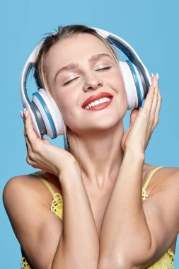Young pretty happy woman in yellow dress listening to music in h