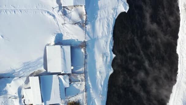 Vzdušné video pohled z nadzvedávání dronu na ruské vesničce v Altajce v zimě. Kamera se dívá dolů. Řeka Kokša s bankami pokryté sněhem. Altai, Sibiř, Rusko