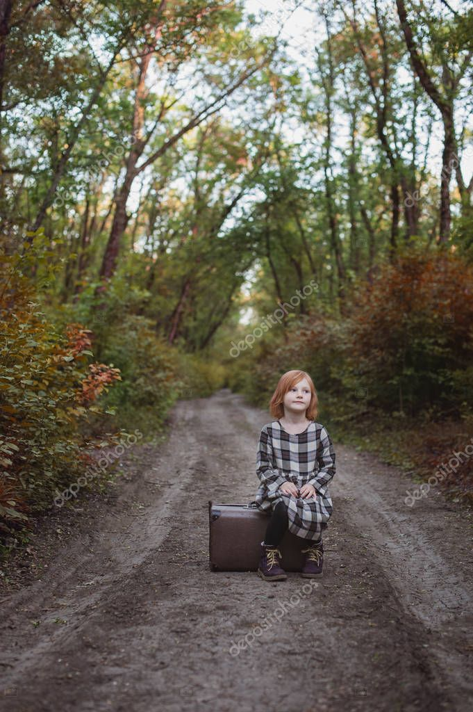 A girl is sitting on an old suitcase on a forest road