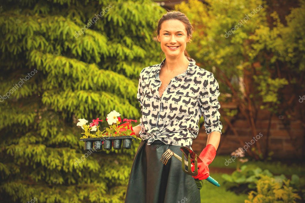 Beautiful smiling gardener with flowers