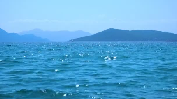 Tengervíz lágy hullámokkal nyáron délben és vitorlás jacht a horizonton, Saronic-szigetek, Görögország