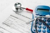 Náklady na zdravotní péči. Stetoskop a kalkulačka symbol pro náklady na zdravotní péči nebo zdravotní insuranc