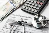 Zdravotní pojištění formulář žádosti s bankovka a stetoskop konceptem pro plánování života