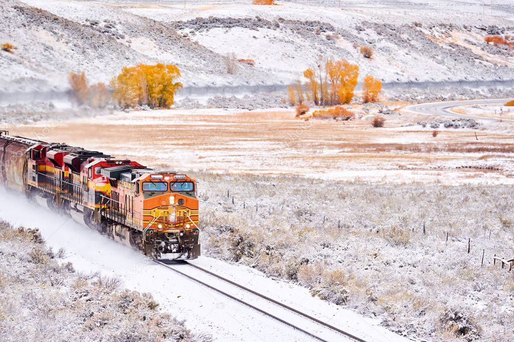 Train transporting tank cars. Season changing, first snow and autumn trees. Rocky Mountains, Colorado, USA.
