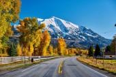 Autostrada con neve coperto montagne rocciose sullo sfondo, Colorado, Stati Uniti dAmerica