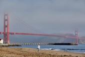 Fotografia Donna che cammina sulla spiaggia vicino al Golden Gate Bridge, San Francisco, California, Stati Uniti