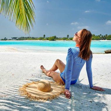 Woman sitting on beach under palm tree