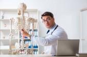 Yong male doktor s kostrou izolované na bílém
