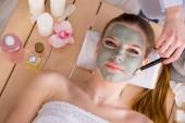 Mladá žena v lázeňské zdravotní koncepce s obličejovou maskou