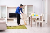 Mladý muž čištění podlahy s koštětem