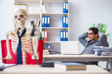 Businessman working with skeleton in office