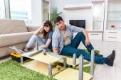 Junge Familie baut Möbel am neuen Haus zusammen
