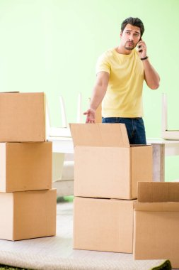 Young handsome man moving in to new house with boxes