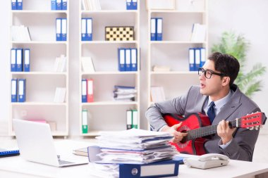 Young handsome businessman playing guitar in the office